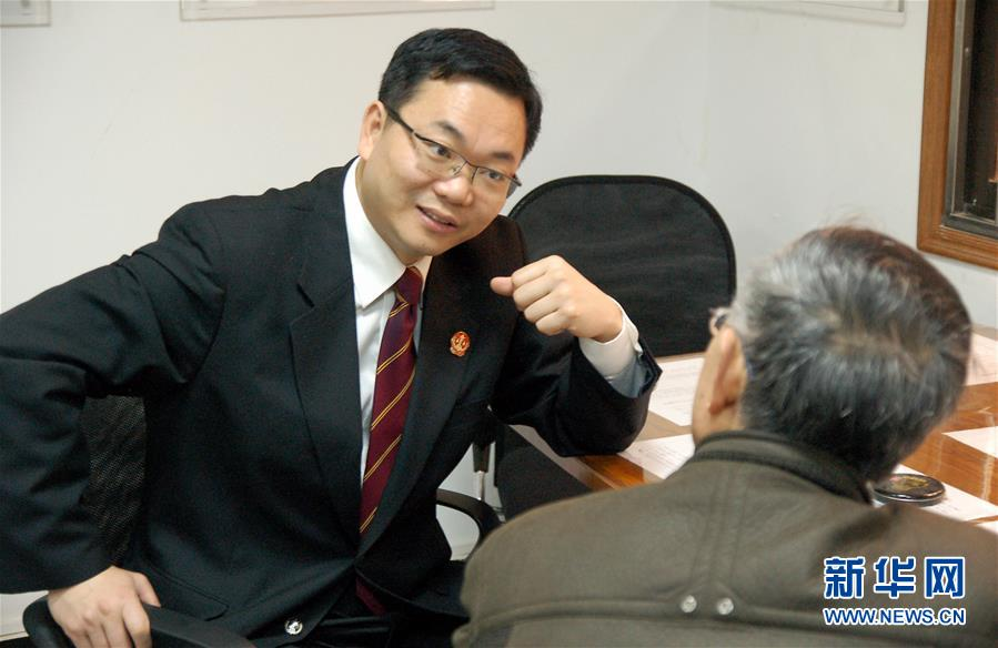 时任上海市长宁区人民法院院长的邹碧华在迎接首诉当事人(2009年2月3日摄)。 新华社发