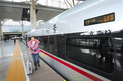 """昨日,北京南站,超长版""""中兴号""""将起程,乘客准备上车。新京报记者 王贵彬 摄"""