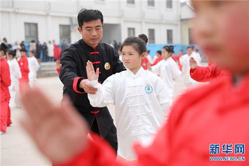 特聘教练和东升在指导学生练习太极拳。