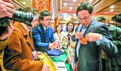 昨天,在北京会议中心,十三届全国人大二次会议北京代表团代表开始报到。图为方复全代表在佩戴证件。 本报记者 武亦彬摄