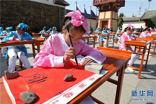 3月12日,许昌曹丞相府,小学生身着汉服在进行书法展示。