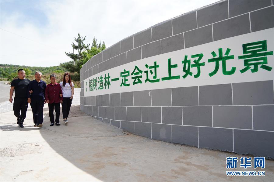 陕西省延安市安塞区雷坪塔村村民张莲莲(右二)与家人一起出门(2018年5月29日摄)。张莲莲与丈夫王耀武用30多年时间在当地造林2000多亩,栽成了超过20万棵树木。 新华社记者 邵瑞