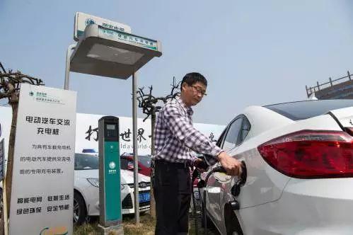 原料图片:别名车主在重庆市内一处停车场为电动汽车充电。(新华社)