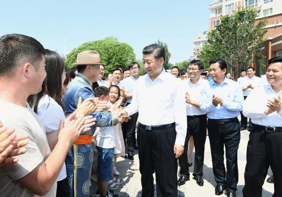 15日,习近平在赤峰市松山区兴安街道临潢家园社区同群众亲切握手。