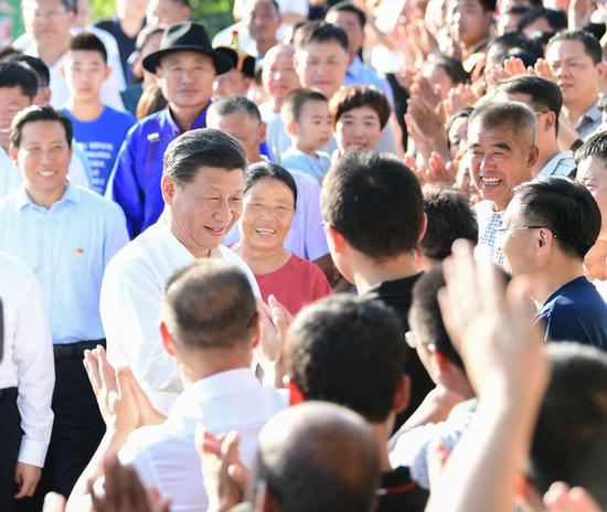 15日,习近平在赤峰市喀喇沁旗河南街道马鞍山村同群众亲切握手。