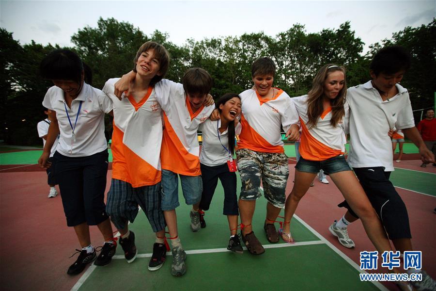 """这是2008年8月2日,在俄罗斯南部黑海之滨的""""小鹰""""全俄儿童中心,在此疗养的中国四川地震灾区的孩子们与俄罗斯学生一起做游戏。新华社记者 沈伯韩"""